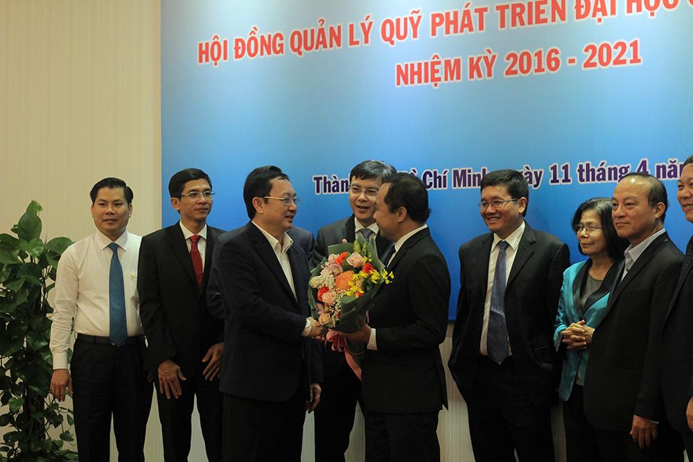 PGS.TS Huỳnh Thành Đạt trao hoa chúc mừng tân PGS.TS Vũ HảiQuân trở thành Chủ tịch Hội đồng Quản lý Quỹ Phát triển ĐHQG-HCM.